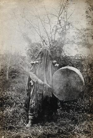 view Minusinsk, Siberia: a Tartar medicine man or shaman in ceremonial dress with a covered face, holding a drum. Photograph, ca. 1920 (?) of a photograph, 1900/1915.