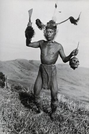 view A young man of the Konyak Naga tribe, India, holding a human head. Photograph.