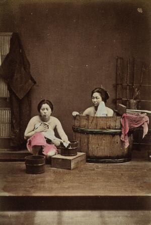 view Japan: two women washing: one bathing in a wooden tub and one squatting down holding a flannel. Coloured photograph, 1870/1890.