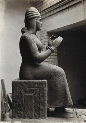 view A sculpture of Gula, Mesopotamian deity of healing, with a dog at her side. Photograph.