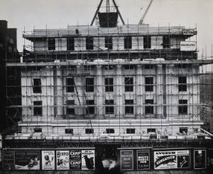 view The Wellcome Research Institution's building, Euston Road, London: east side covered in scaffolding during construction by Trollope & Colls, 1931. Photograph.