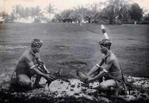 view Sarawak: two native Sea Dayaks at a cockfight. Photograph.
