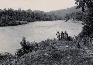 view Sarawak: three men standing by the Baram River. Photograph.