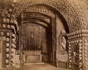 view An altar bearing a Latin inscription surrounded by an array of human skulls and bones and a cloaked skeleton. Photograph by J. Taylor, c. 1881.