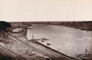 view East London, South Africa: a jetty and buildings near the mouth of the Buffalo River. Woodburytype, 1888, after a photograph by Robert Harris.