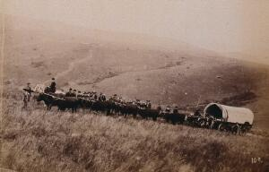 view South Africa: landscape with people, a wagon and oxen in the foreground. 1896.