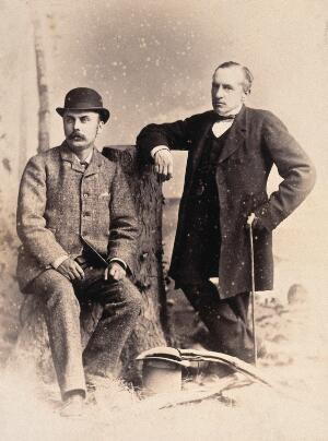 view Two American men: studio portrait: one seated on a tree stump, one standing, leaning on the tree stump. Photograph, ca. 1880.