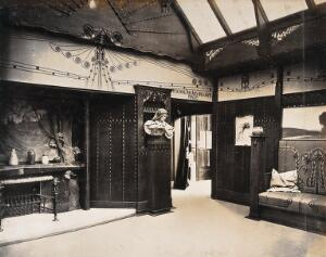 view The 1904 World's Fair, St. Louis, Missouri: the Prague School for Arts and Crafts exhibit: an art nouveau interior with a decorative fireplace and wooden panelling. Photograph, 1904.