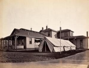 view Hospital of the Medical Department of the U.S. Army, Philadelphia: with hospital tents outside. Photograph, 1876.