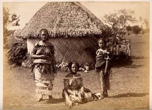 view Nuku'alofa, Tonga: three Tongan women in front of a traditional hut. Albumen print by Burton Bros.
