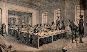 view A classroom with children sitting at long tables and a teacher standing with a book in her hand. Lithograph by J.B. Sonde.