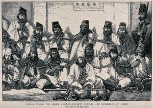view Men in hats are sitting on the ground in a group bound together by chains. Wood engraving.