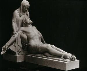 view Pieta: Jesus Christ with outstretched legs supported by the Virgin Mary. Photograph, ca. 1934, of a sculpture by Helen V. Mackay, 1932.