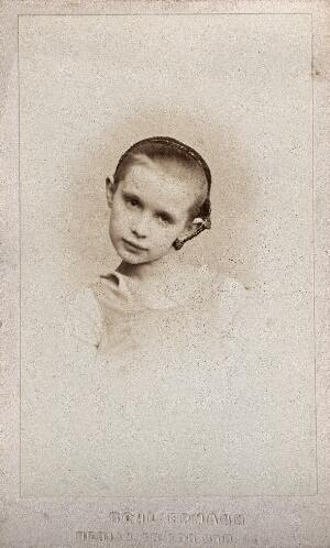 view A young girl wearing a hairnet, head tilted to one side: a vignetted head-and-shoulders portrait. Photograph, 1870/1890.