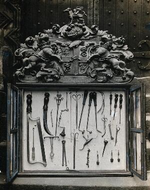 view The Barber Surgeons' Guild of Newcastle: surgical instruments in a display case bearing the Guild's coat of arms. Photograph, ca. 1926.