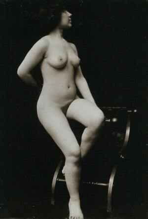 """view A young woman, posing naked in a photographic studio, sitting on the arm of a """"Roman"""" chair. Photograph, ca.1900."""