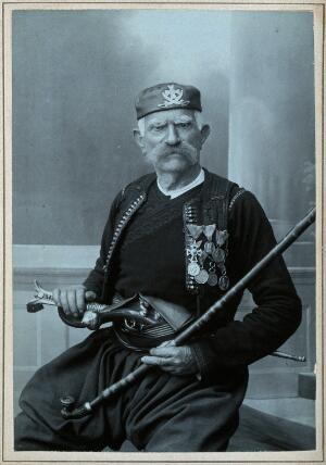 view An elderly Serbian man, wearing national dress with many medals, with a pistol in his belt and holding a tobacco pipe. Photograph by D. Djordjevic, first quarter of the twentieth century.