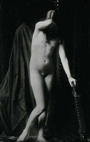 view An adolescent girl, posing naked leaning on the back of a chair, in a makeshift photographic studio. Photographic postcard, ca.1920.