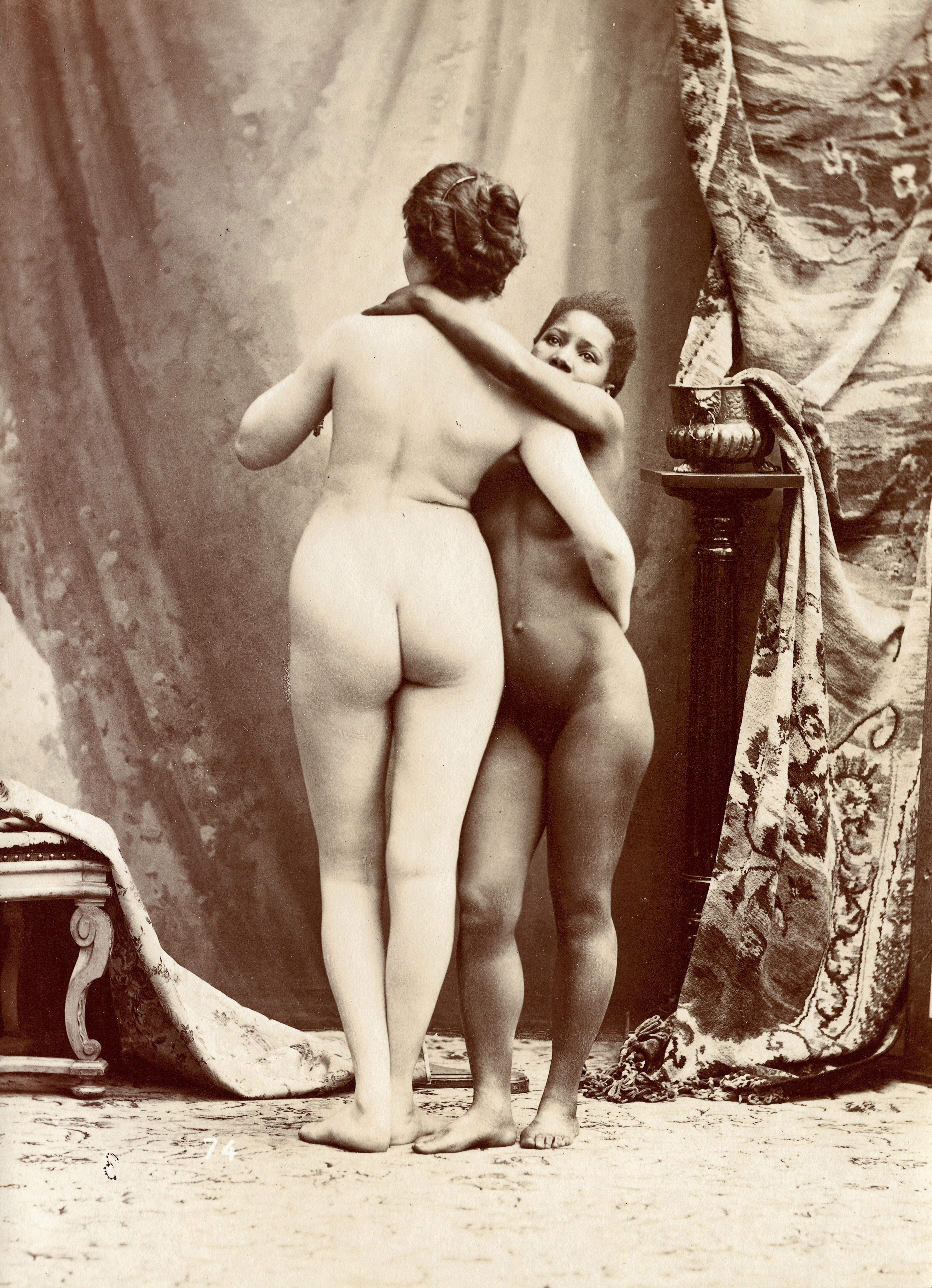 Two women posing naked in a photographic studio, standing ...