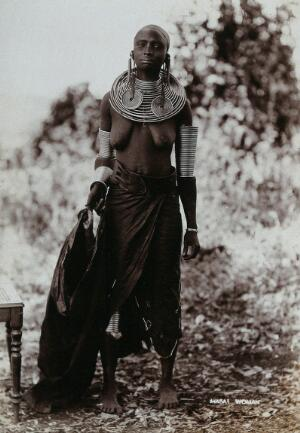 view A young Masai tribeswoman, full length, wearing much jewellery. Photograph, ca.1900.