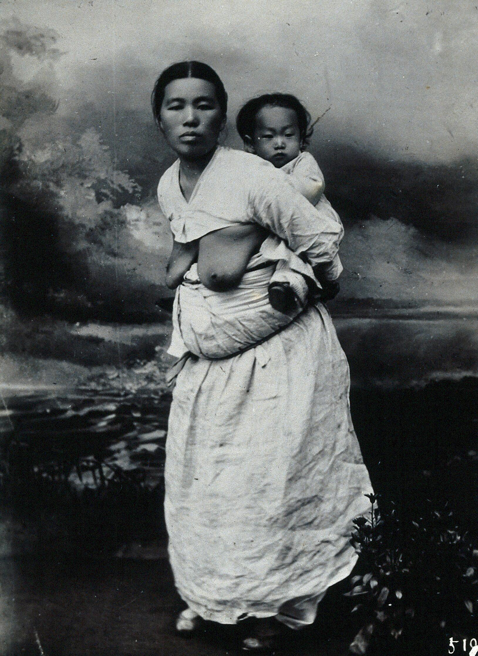 A Korean (?) woman, carrying a baby on her back ...