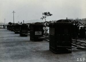 view A line of sedan chairs waiting beside a railway track, in Korea. Photograph, ca.1900.