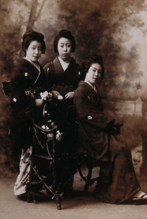 view Three young women posing in a photographic studio, one seated on a bench, in front of a painted backdrop of a rural scene. Photograph by K. Ogawa, first decade of the twentieth century.