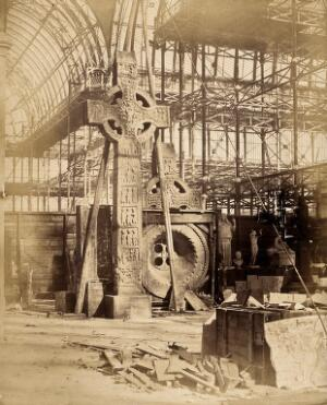 view The Crystal Palace during its re-erection at Sydenham, London: a large celtic cross and other statues in the unfinished interior. Photograph by Philip Delamotte, ca. 1854.
