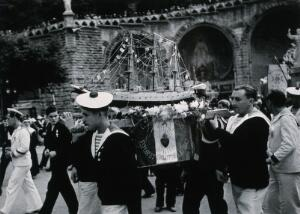 view Lourdes, France: sailors carrying a model of a ship amidst crowds of pilgrims. Photograph, ca. 1937.