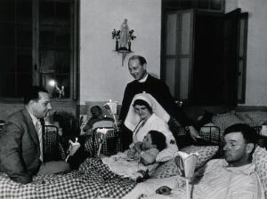 view Lourdes, France: a hospital ward: a priest and a nurse by the bed of a boy. Photograph, ca. 1937.
