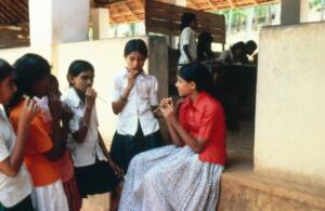 view Schoolgirls cleaning teeth with neem twigs in India