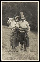 view Harry Smallwood and another man stand in a field, one in drag and the other wearing Turkish inspired costume. Photographic postcard, 1925-.