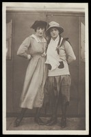view Two men, both in drag, pose wearing hats and make-up. Photographic postcard, ca. 1918.