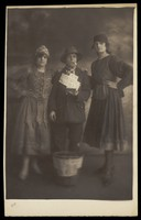 view Three actors in drag, posing in a variety of costumes; in front of a basket on the floor. Photographic postcard, 191-.