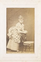 view A man in drag resting against a chair. Photograph, 187-.