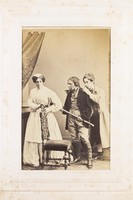view Three men, one in drag, acting out a scene. Photograph, 189-.