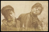 view Two boys posing with cigarettes. Photographic postcard by A. Caggiano, 190-.