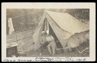 view Two men outside their tent at Camp Tecumseh, near Schenectady, New York. Photographic postcard, 1912.