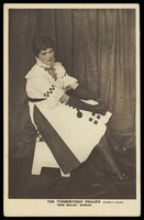 """view A British prisoner of war in drag, performing for """"The Timbertown Follies"""", at a prisoner of war camp in Groningen. Photographic postcard, 191-."""
