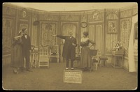 """view Amateur actors, some in drag, posing on stage for """"Miquette & sa mere""""; at Sennelager prisoner of war camp in Germany. Photographic postcard, 191-."""