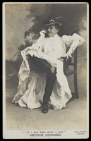 view Arthur Lennard in drag over his male clothing, smoking a cigar. Photographic postcard, 19--.